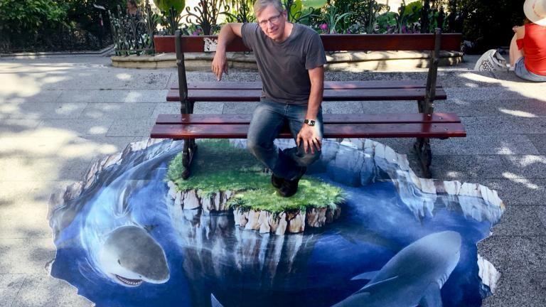 Un pallier de l'escalier Denis-Papin recouvert d'une anamorphose donnant l'illusion visuelle qu'un trou rempli d'eau est habité par des requins. L'auteur pose à côté.