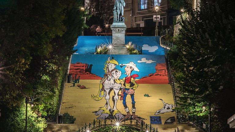Photo de nuit de l'ensemble de l'escalier revêtu du décor de Lucky Luke, Jolly Jumper, Rantanplan et Joe Dalton.