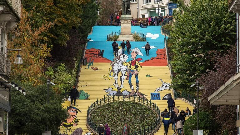 Photo de jour del'escalier revêtu du décor de Lucky Luke, avec de nombreuses personnes montant et descendant l'escalier.