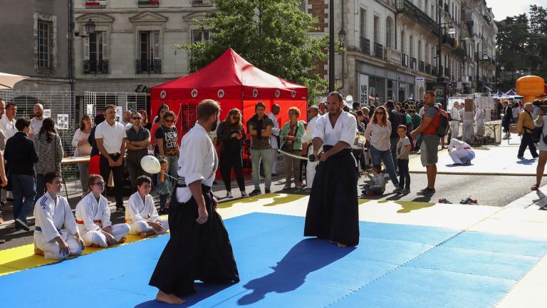 Des hommes pratiquent un sport de combat avec sabre, sur un tatami installée rue Denis-Papin.