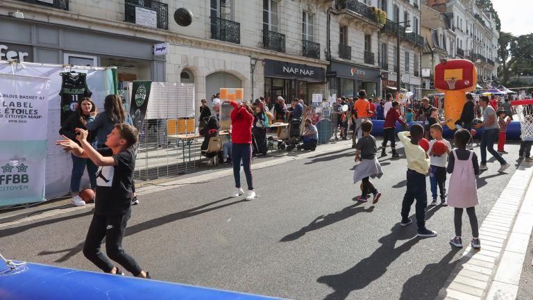 Des enfants pratiquent du basket-ball sur un terrain installé rue Denis-Papin.