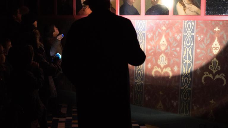 Visite nocturne du Château royal : le guide éclaire avec une lampe torche la galerie de la reine Catherine de Médicis, composée de nombreux portraits.
