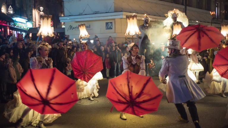 Les danseurs et danseuses font tourner leurs parapluies et jouent avec leurs costume et chapeaux éclairés.