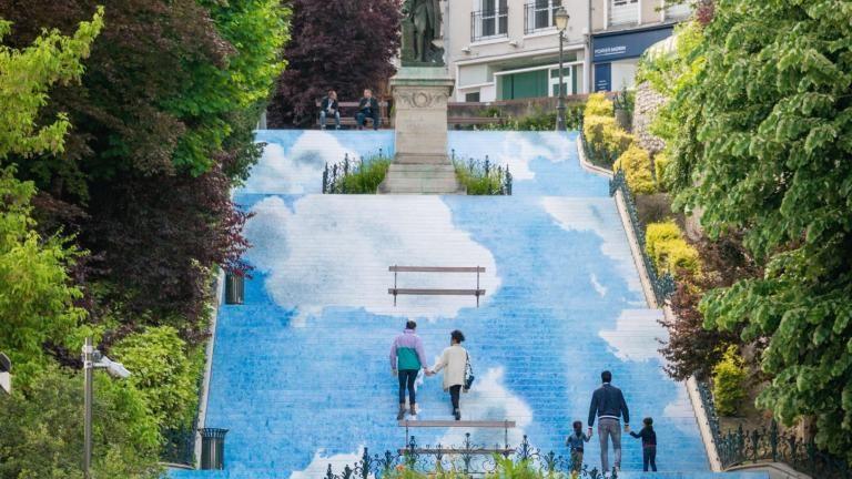 Toutes les contre-marches de l'escalier sont recouvertes de bandes formant dans l'ensemble un immense ciel bleu avec quelques nuages, sur lequel marchent les passantes et les passants.