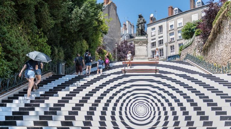 Des personnes montent l'escalier Denis-Papin, dont les contremarches sont recouvertes pour former une immense spirale noir et blanc.