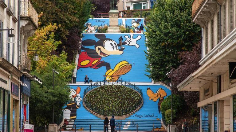 Les contremarches de l'escalier Dennis-Papin de Blois sont décorées pour former une immense bande dessinée. Mickey court dans la grande case au milieu, Donald et Pluto le regardent dans une case en bas, et Clarabelle et Minnie lisent dans leur case en haut. L'escalier est bordé par de grands arbres feuillus. Des personnes montent, descendent ou sont assises dans l'escalier.