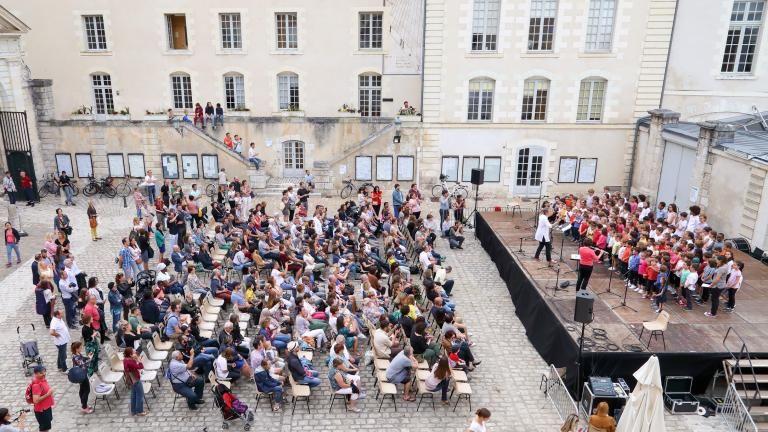 La chorale de l'école du Foix chante sur scène. Le point de vue en hauteur inclut les nombreuses personnes présentes.
