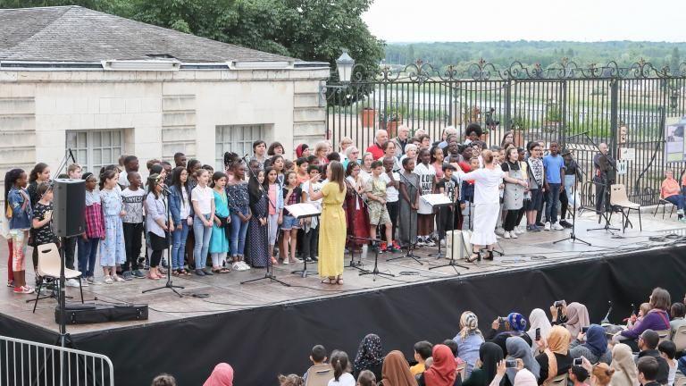 La chorale de l'école Jules-Ferry chante sur scène, devant de nombreuses personnes.