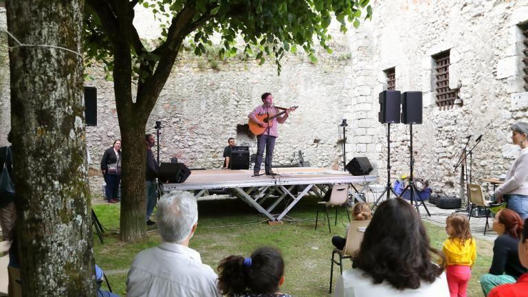 Un guitariste acoustique se produit sur la scène ouverte de la Tour Beauvoir.