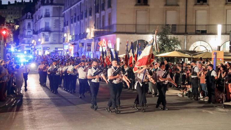 Les troupes défilent dans le centre-ville, avec les porte-drapeaux en tête de file.