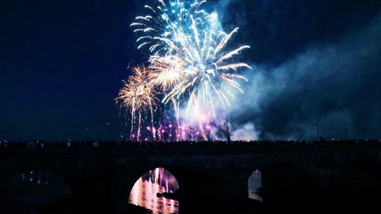 Le feu d'artifice multicolore de 2019, tiré au-dessus de la Loire, avec le pont Jacques-Gabriel et la foule au premier-plan.