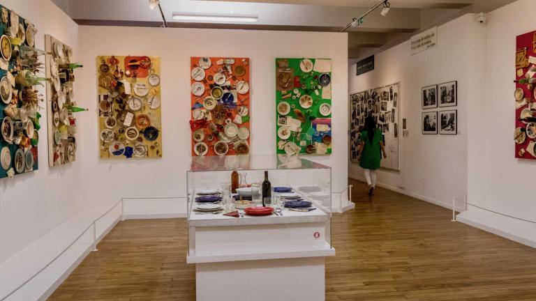 Collages des objets et aliments formant une table de repas, sur douze tableaux accrochés aux murs. Un treizième tableau est exposé à l'horizontale.