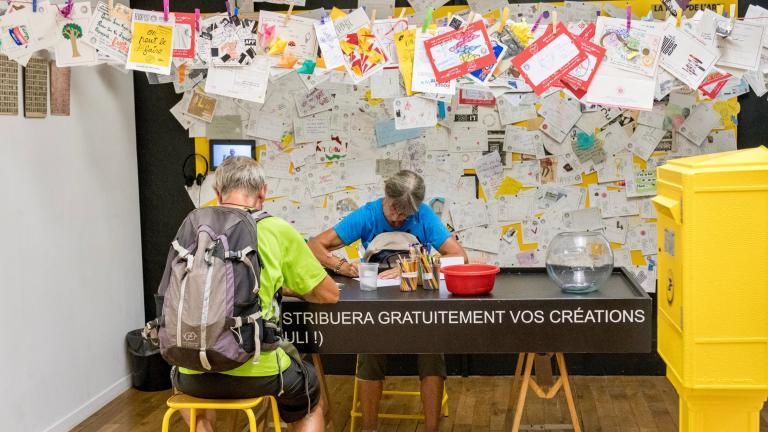 Deux personnes écrivent des cartes postales, autour de centaines de cartes épinglées en l'air ou sur des murs. Une boîte aux lettres de La Poste est représentée au premier plan.