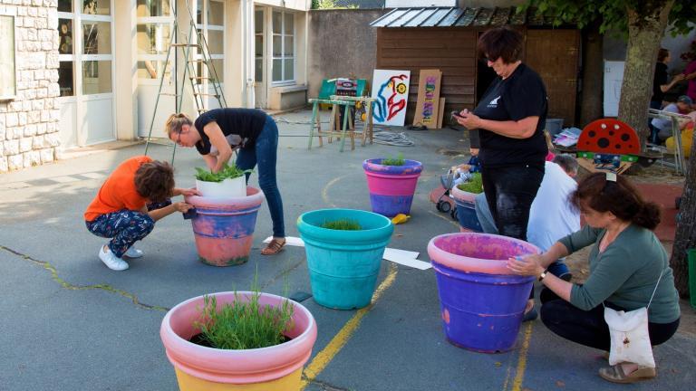 Des personnes peignent des gros pots de fleurs avec des couleurs vives.