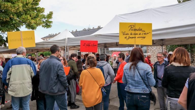 Des personnes au milieu de la foule tiennent des pancartes pour rassembler autour d'elles celles inscrites à leur atelier.