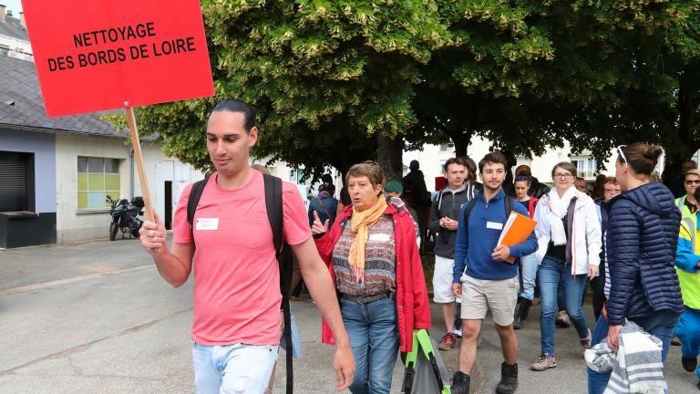 Une personne tenant une pancarte «nettoyage en bord de Loire» guide les autres vers le fleuve.