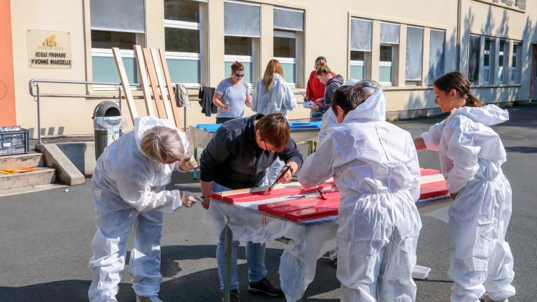 Des personnes s'attèlent à de la peinture dans la cour de l'école Yvonne-Mardelle.