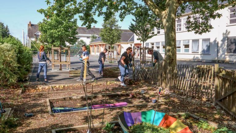 Des personnes posent une nouvelle barrière autour des jardins de l'école Yvonne-Mardelle.