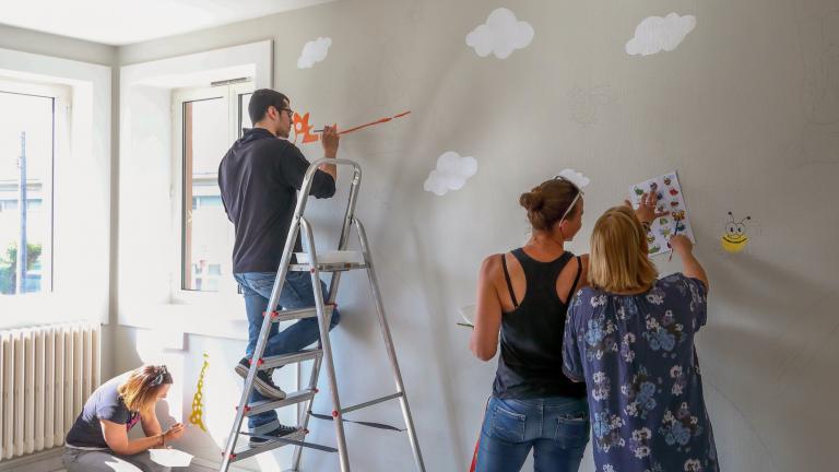 Des personnes peignent des nuages et une abeille sur les murs d'une école.