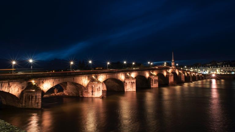 Le pont Jacques-Gabriel mis en lumière avec une teinte orangée respectant la biodiversité.