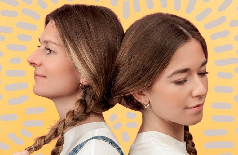 Portrait du groupe Les Frangines, les deux sœur se tournant le dos, chacune ayant la tête posée contre celle de l'autre et leur cheveux ne formant qu'une seule tresse.
