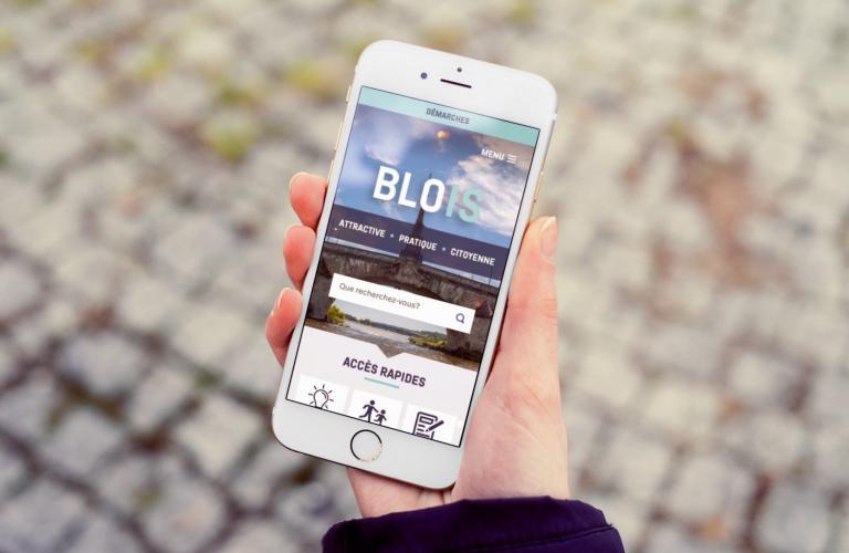 Un smartphone tenu en main, affichant la page d'accueil de Blois.fr.