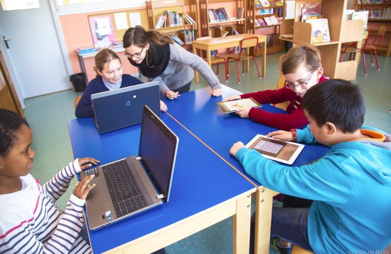 Des enfants s'exercent sur des ordinateurs et des tablettes.