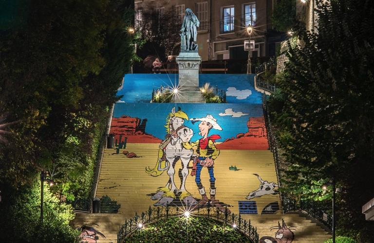 Photo d'ensemble de l'escalier, dont les contremarches sont entièrement recouvertes pour former un dessin de Lucky Luke et ses compagnons dans son univers.