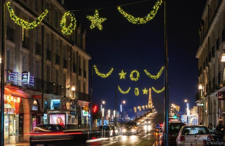 Décorations de fin d'année illuminant la rue Denis-Papin et le pont Jacques-Gabriel en arrière-plan.