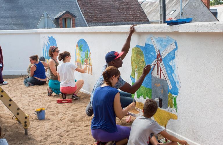 Des personnes de tous les âges peinent des dessins sur le mur d'une 'aire de jeux.