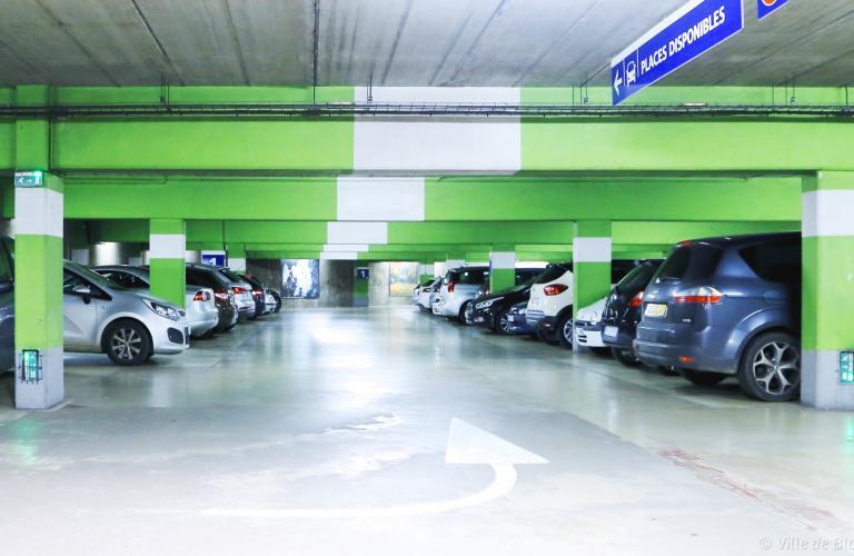 Des voitures sont stationnées dans un parc souterrain.