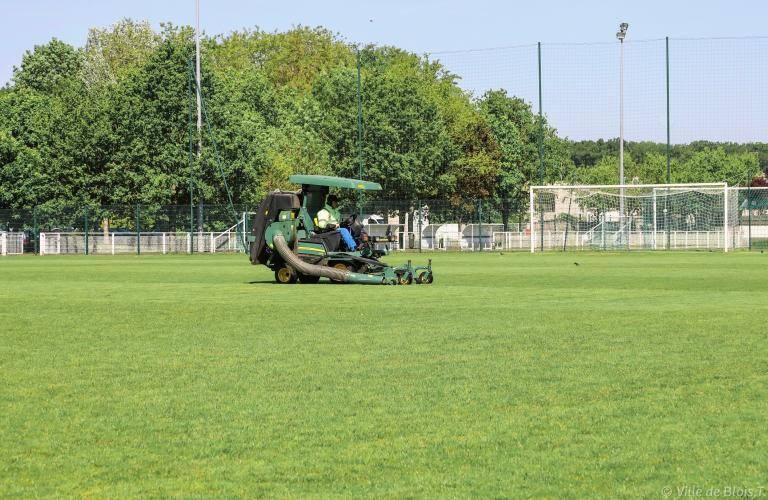 Un véhicule-tondeuse entretient la pelouse du stade des Allées (Jean-Leroi).