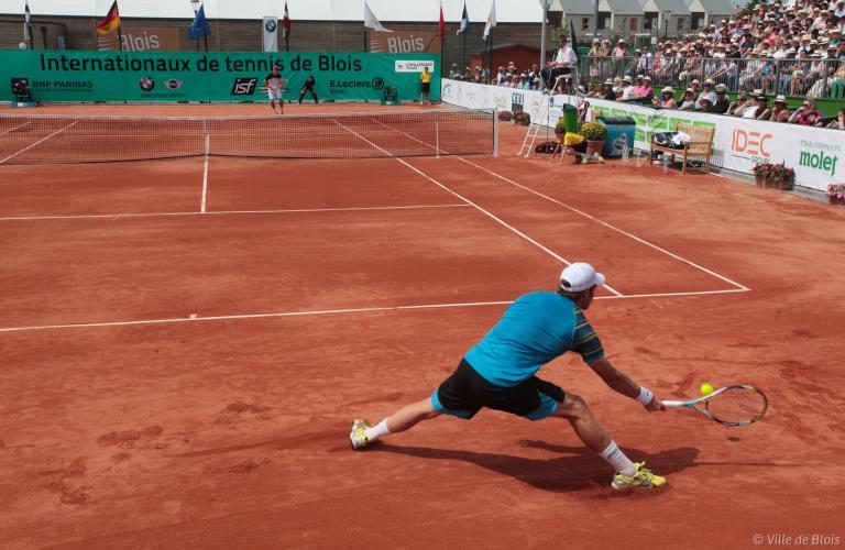 Un tennisman glisse sur la terre battue pour frapper une balle.