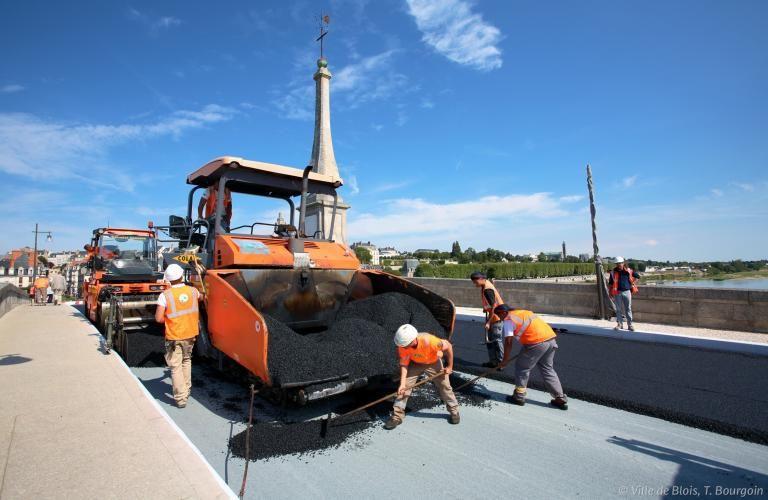 Des ouvriers travaillent sur le nouveau revêtement de la chaussée du Pont Jacques-Gabriel.