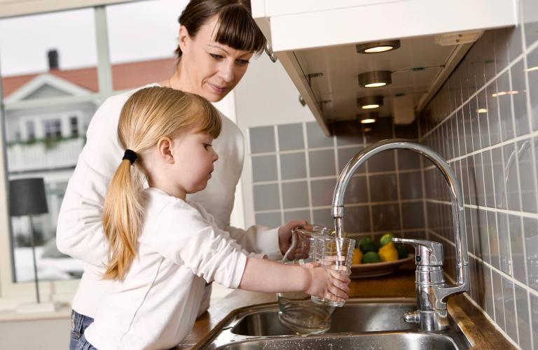 Une petite fille se verse de l'eau dans un verre sous les yeux d'une adulte.