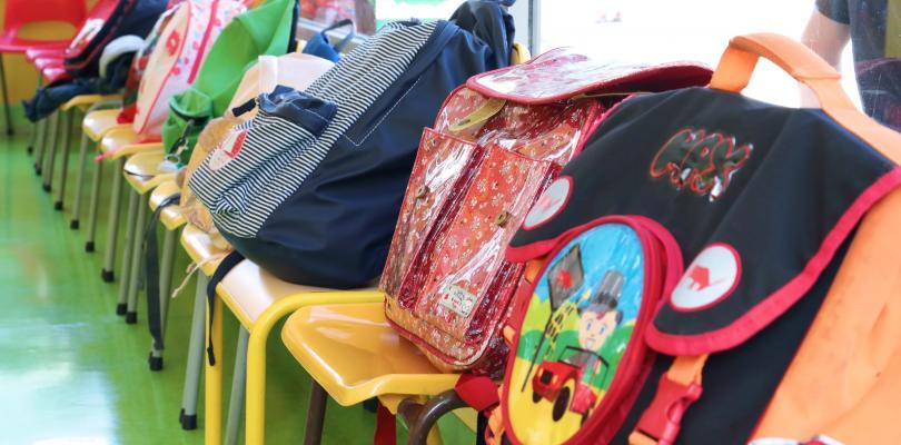 Des cartables sont posés sur des chaises en enfilade.