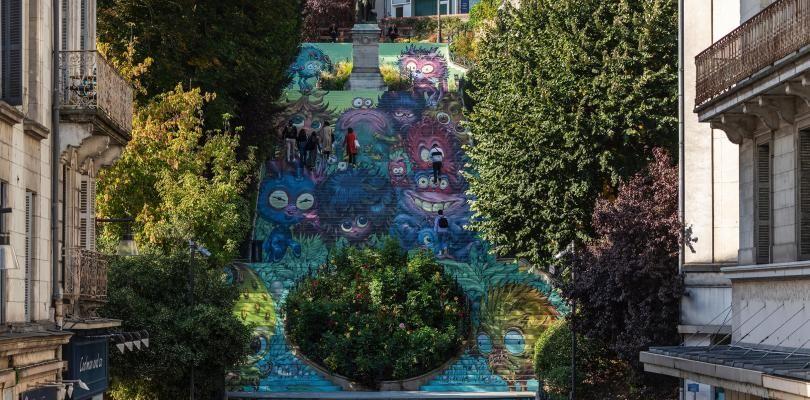 Photo d'ensemble de l'escalier, dont les contremarches sont décorées pour ensemble former une illustration d'un groupe de monstres de Stan Manoukian. Des personnes descendent et montent l'escalier.