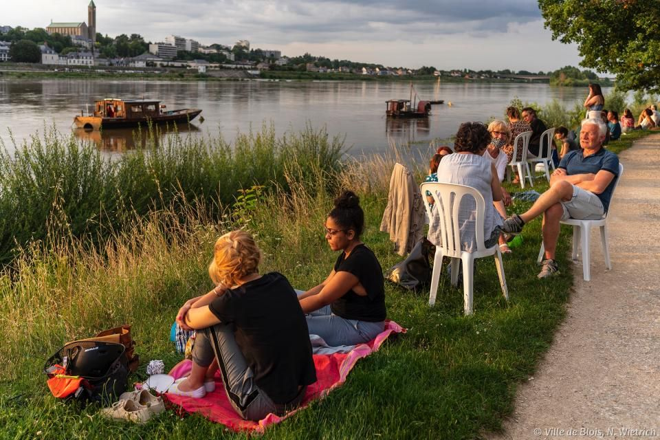 Bords de Loire au niveau du port de la Creusille : des petits groupes se forment sur la pelouse pour discuter, boire un verre, manger, etc. Un fûtreau est à proximité. La basilique est à l'arrière-plan, de l'autre côté de la Loire. Le soleil s'apprête à se coucher.