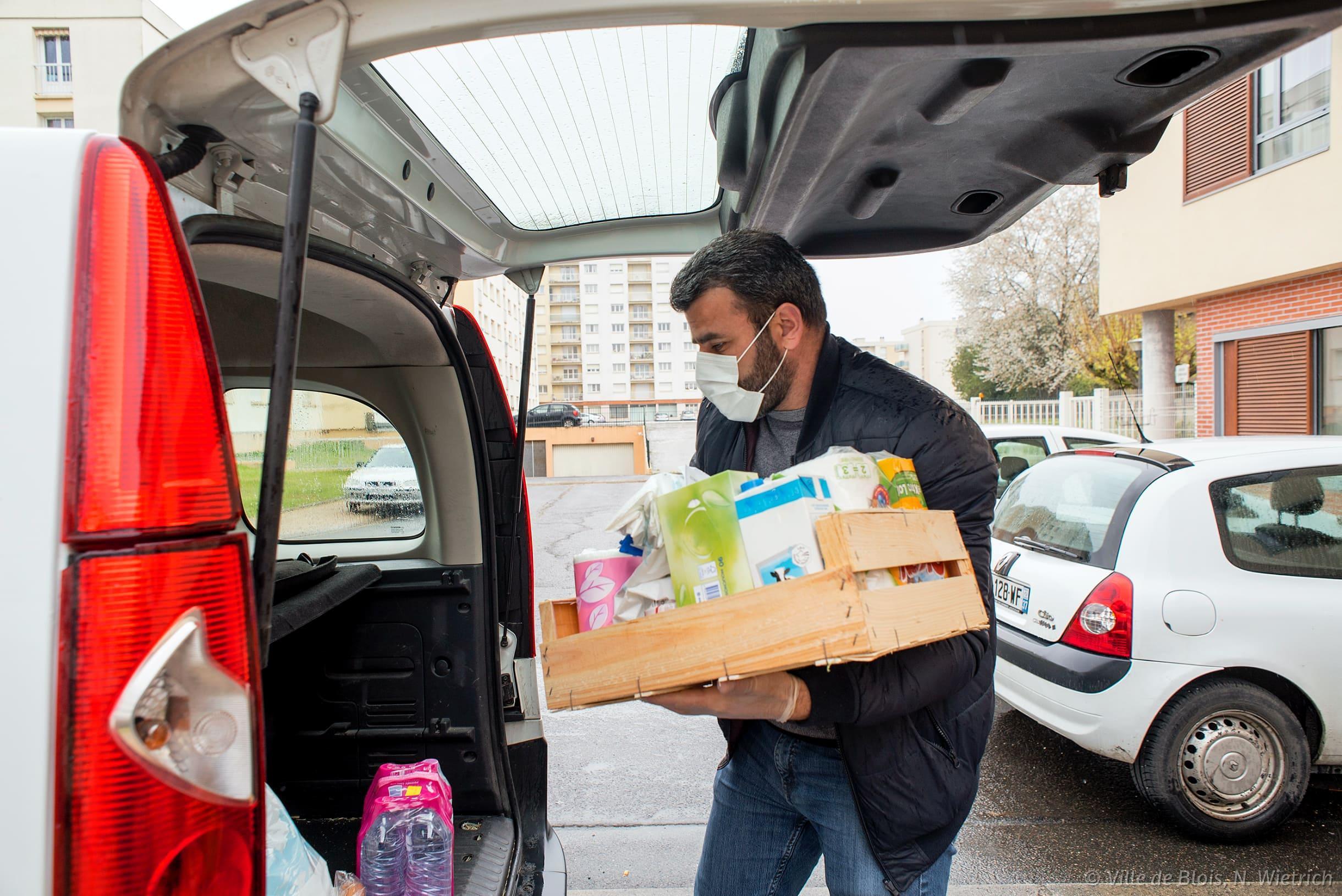 Ozgur Eski, conseiller municipal, décharge des courses dans le véhicule de la Ville pour les livrer aux personnes ne pouvant pas se déplacer.