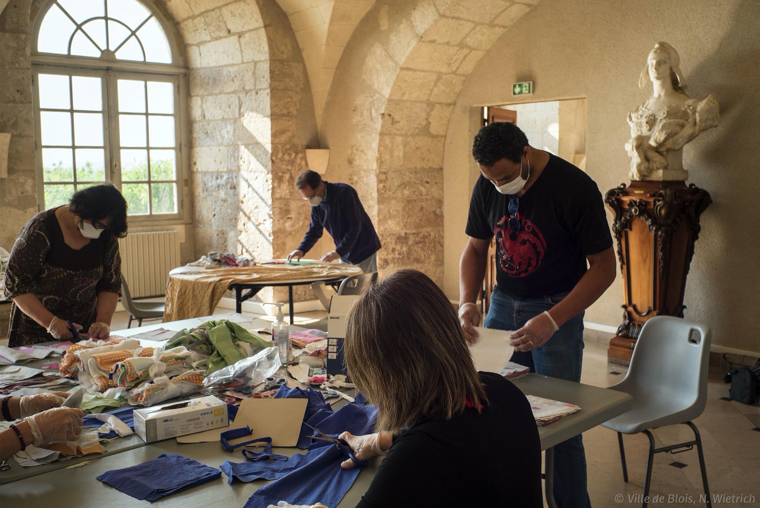 Quatre personnes dans une salle dédiée à la découpe du tissu pour en faire des masques.