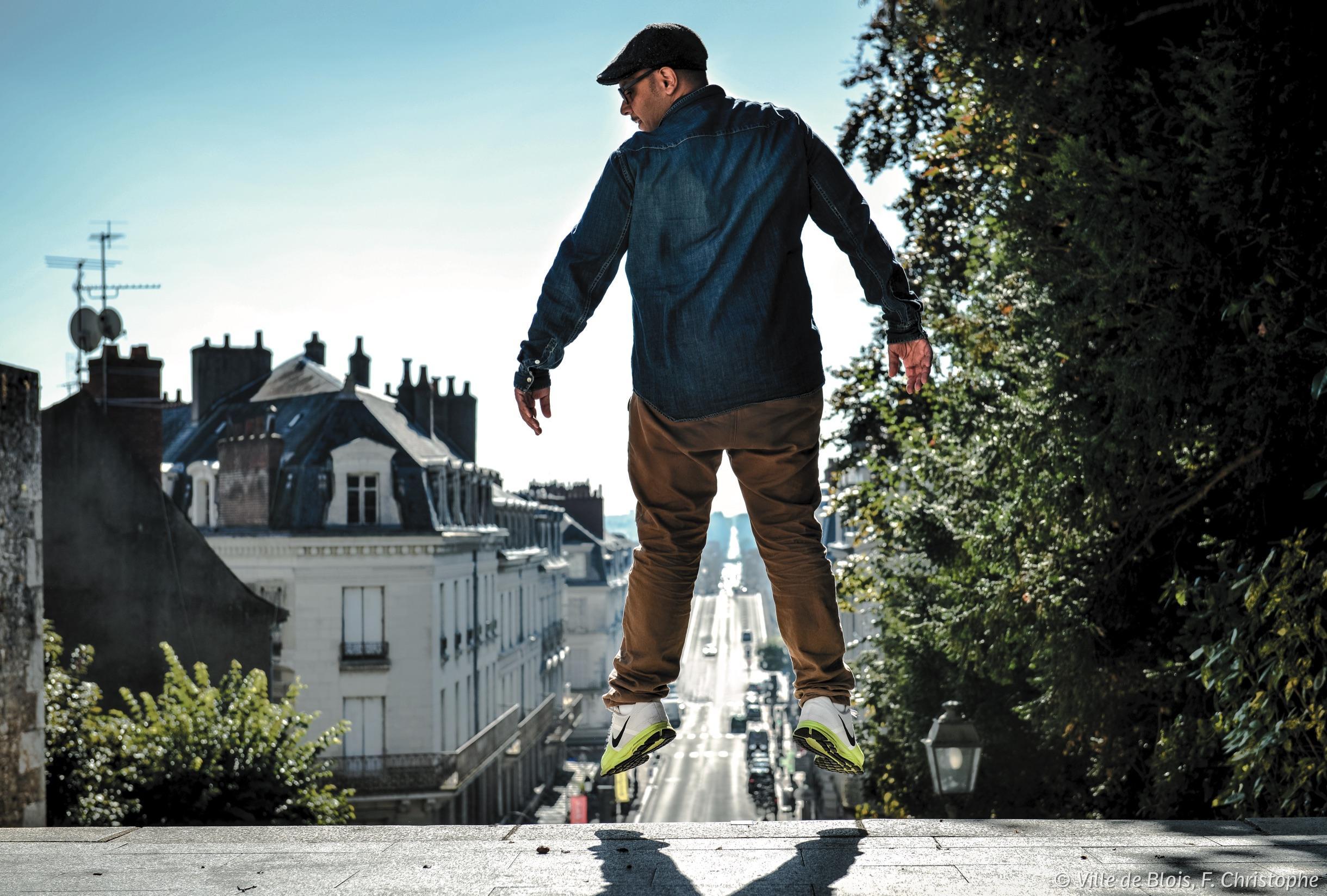 Du haut de l'escalier, une personne saute, laissant entrevoir entre ses jambes la perspective de plusieurs kilomètres de long menant à Saint-Gervais.
