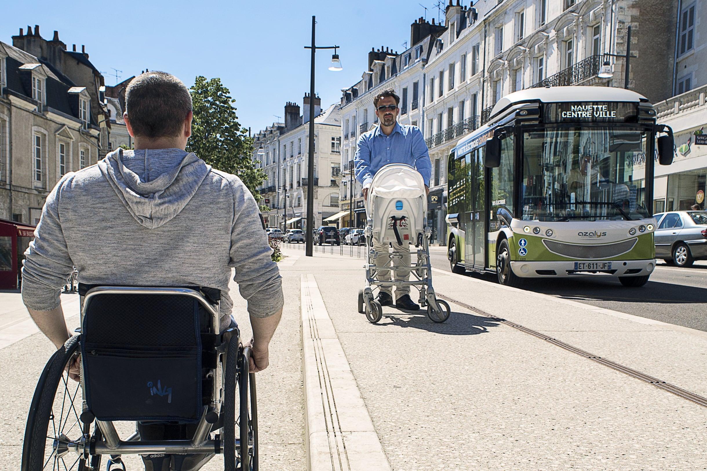 Une personne en fauteuil roulant croise une personne avec une poussette sur un trottoir accessible et doté d'une bande de guidage podotactile.