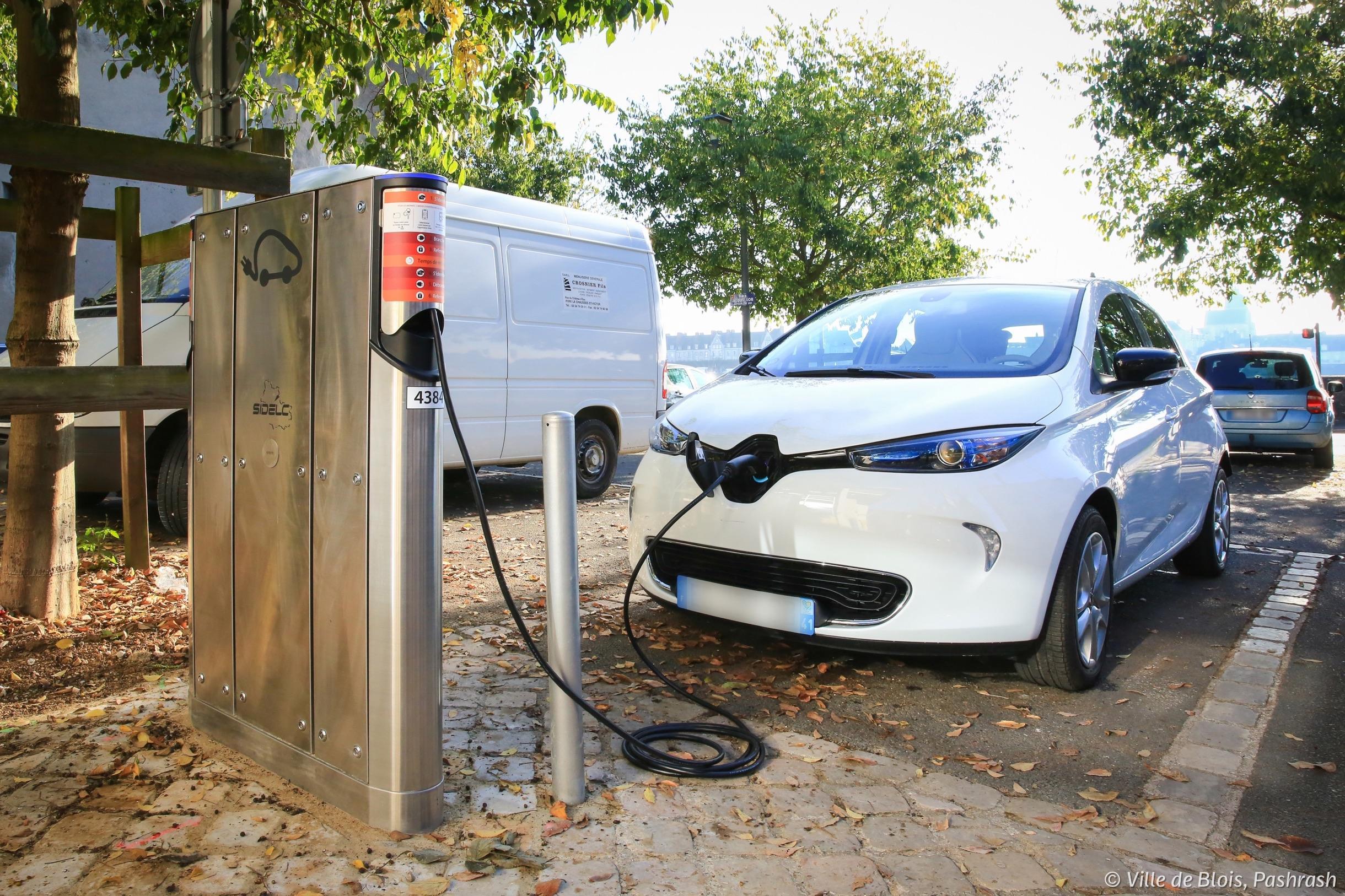 Une voiture en train d'être rechargée par une borne électrique.