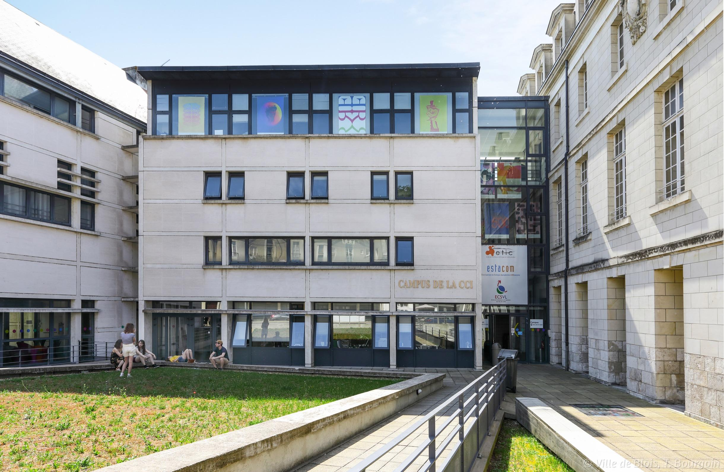 Façade du campus de la chambre de Commerce et d'Industrie, avec une pelouse occupée par plusieurs étudiantes et étudiants.