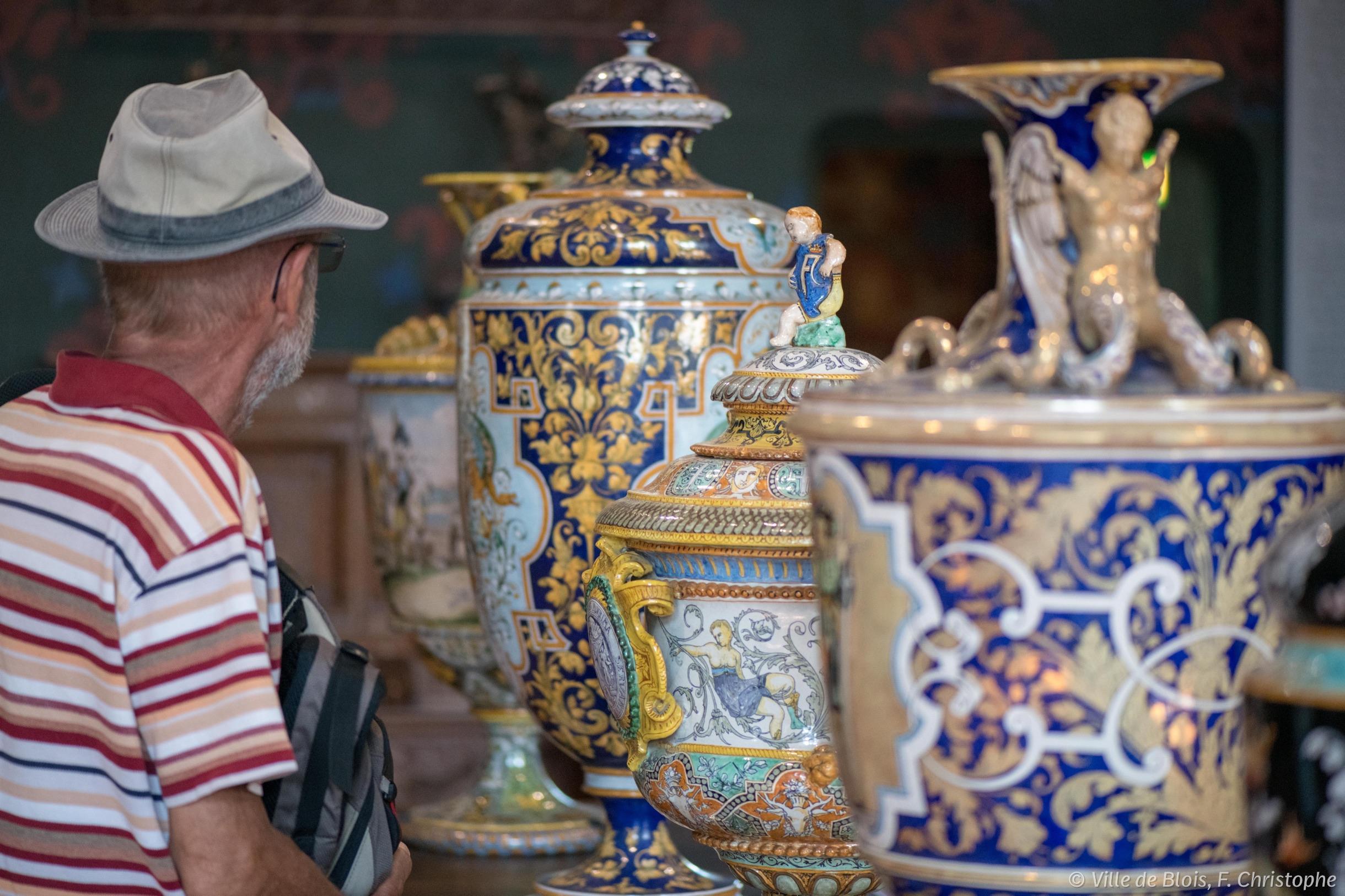 Les vases en céramiques, peints, exposés dans les appartements royaux du Château royal, regardés de près par un visiteur.