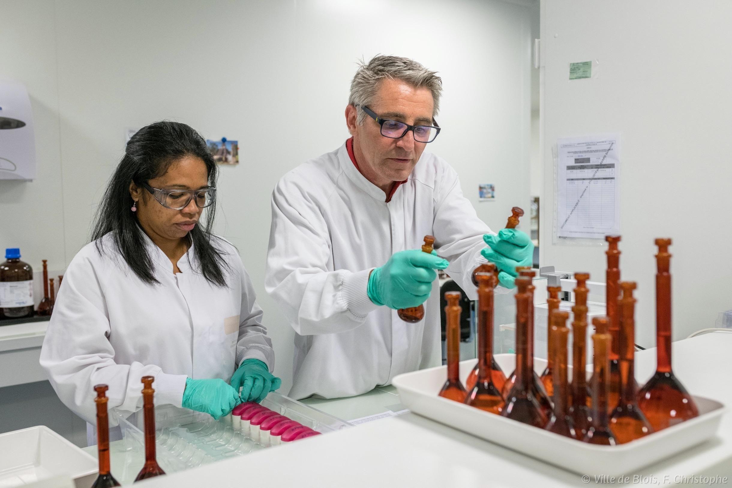 Une femme et un homme travaillent autour de fioles pour l'entreprise pharmaceutique Chiesi.