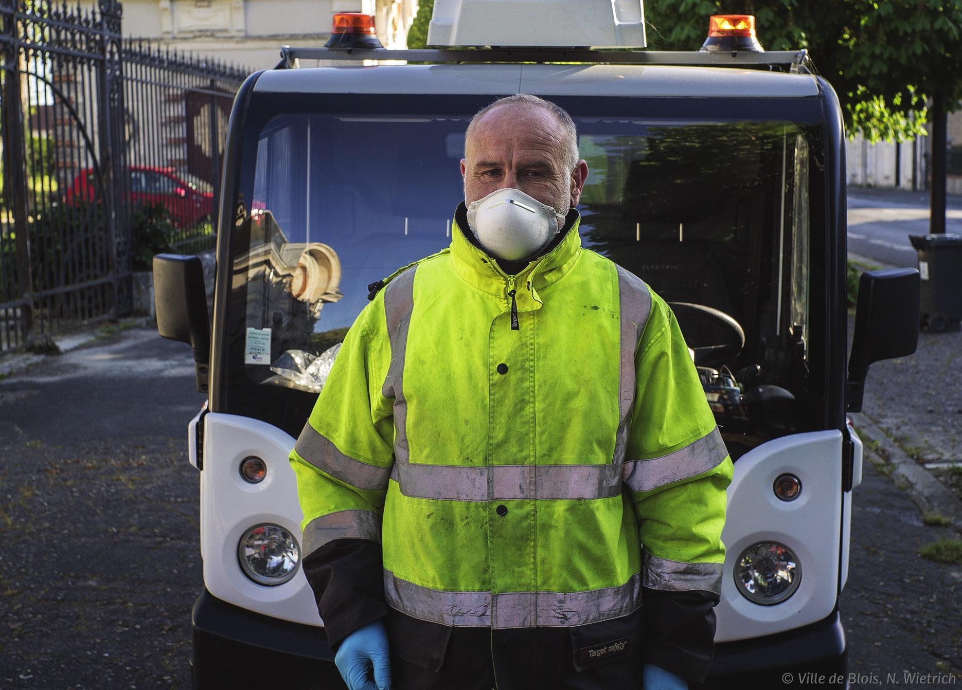 Un agent du service propreté équipé d'un masque devant son véhicule de travail.