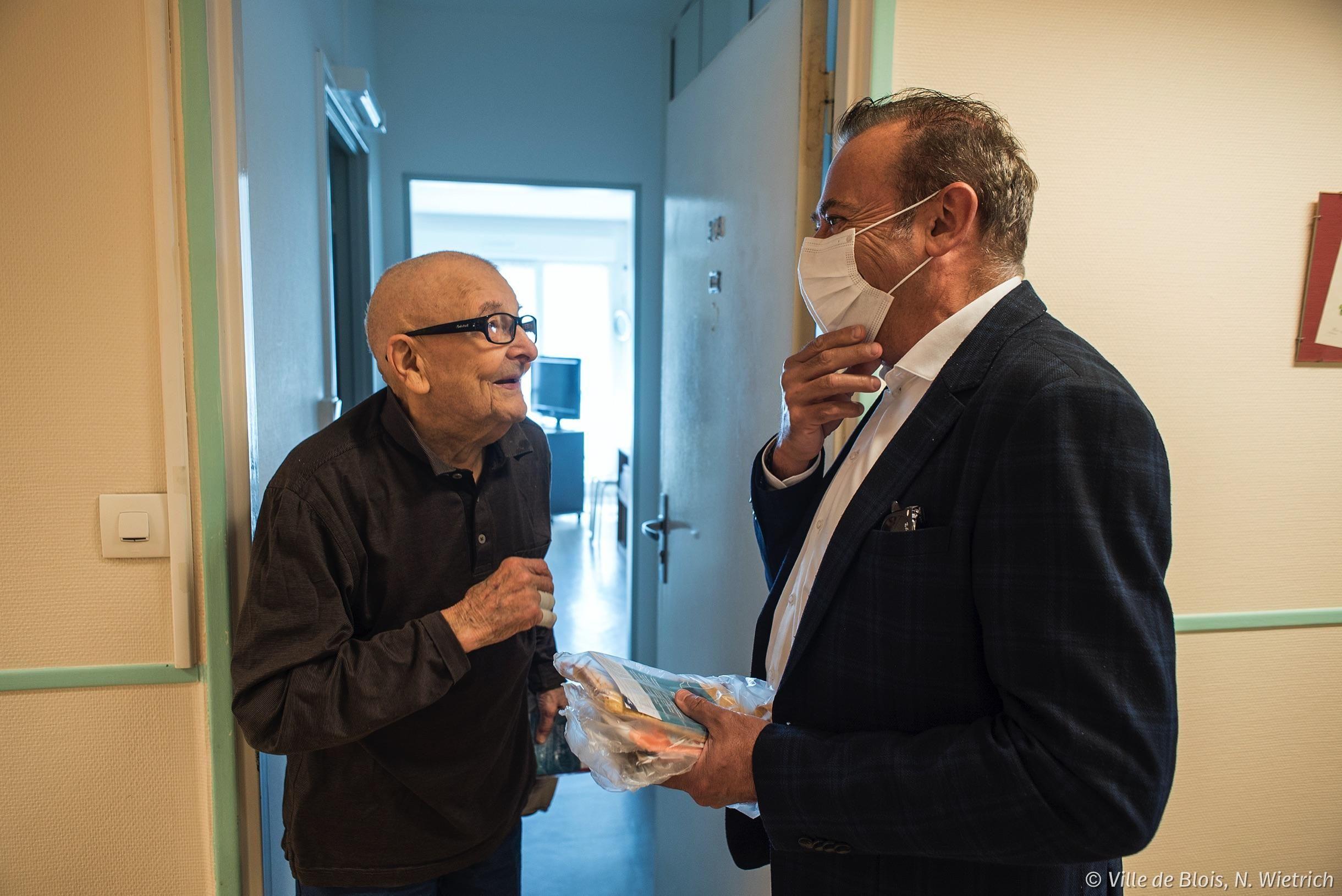 Le maire donne un masque à un usager d'une résidence-autonomie.