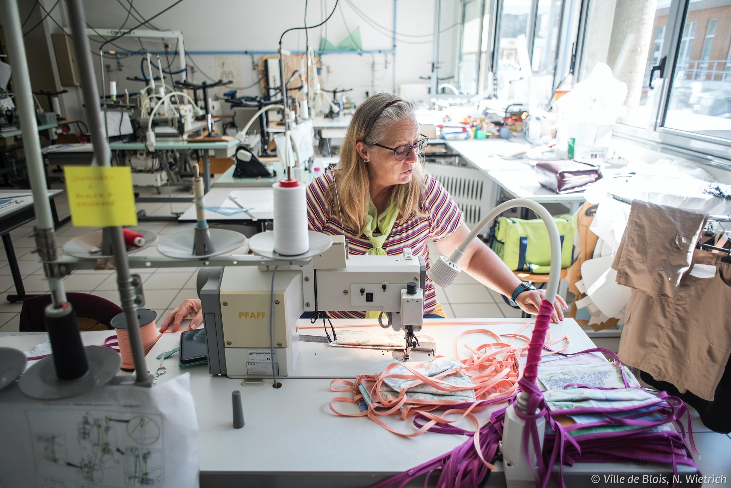 Une agente de la Ville utilise le matériel de couture du lycée Delaunay pour fabriquer des masques.