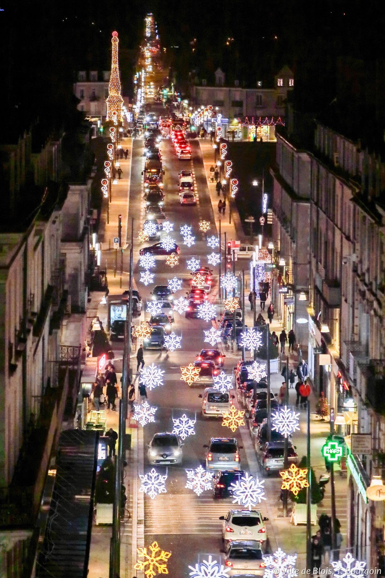 La rue Denis-Papin est illuminée par des luminaires suspendus en forme de flocons de neige. Le Pont Jacques-Gabriel est visible en arrière-plan.